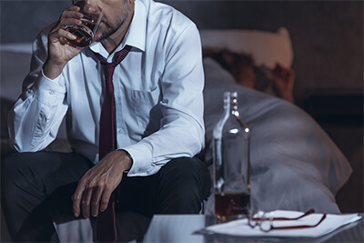 Stressed man sitting in a dark room with a bottle and glass with alcohol