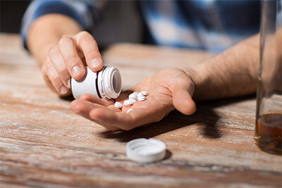 unhappy drunk man with bottle of alcohol and pills committing suicide by overdosing on medication at night